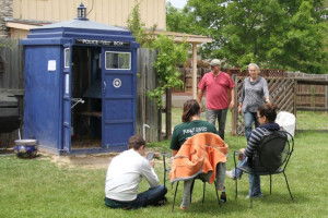 A group of attendees sit and stand near a coop that looks like a phone booth from the sci-fi show Doctor Who.
